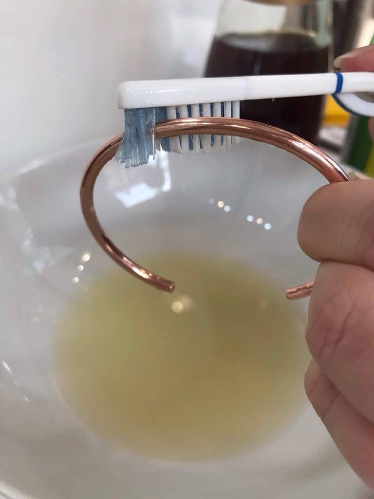 Lady cleaning a Trollbeads Copper Bangle with toothbrush