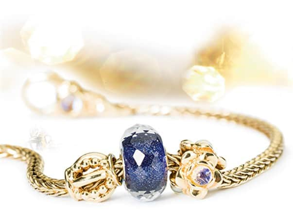 Gold Trollbeads bracelet and charm beads with blue faceted glass bead