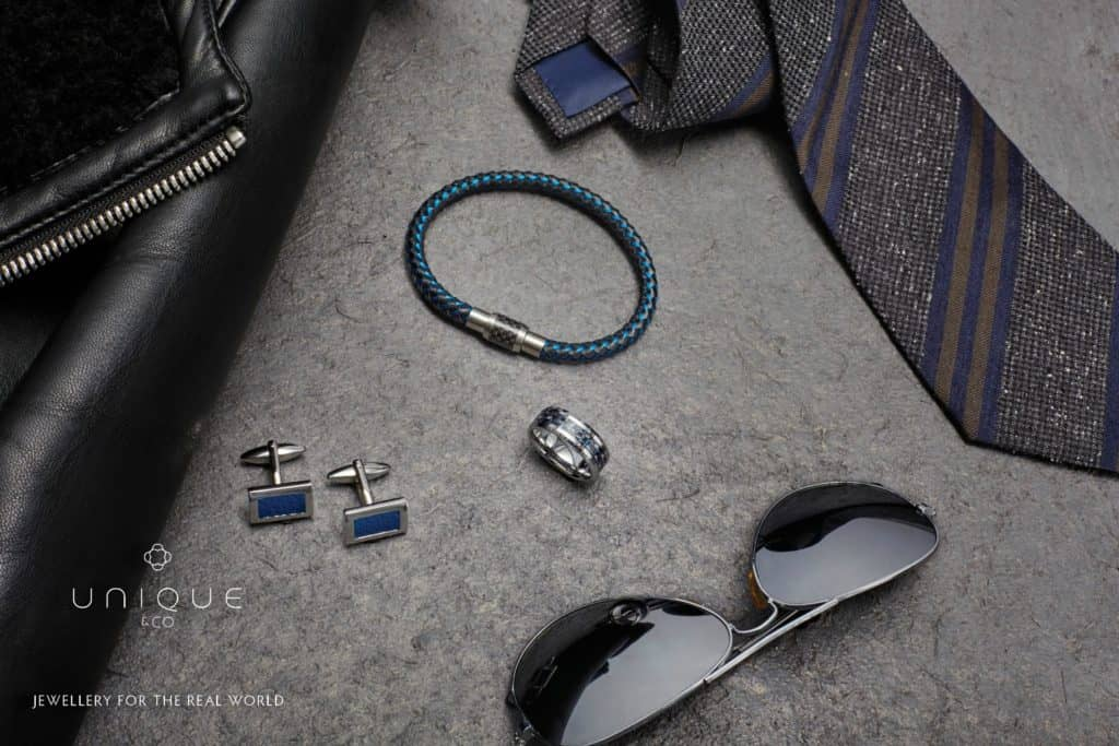 Men's clothing laid out with sunglasses, tungsten ring and leather bracelets