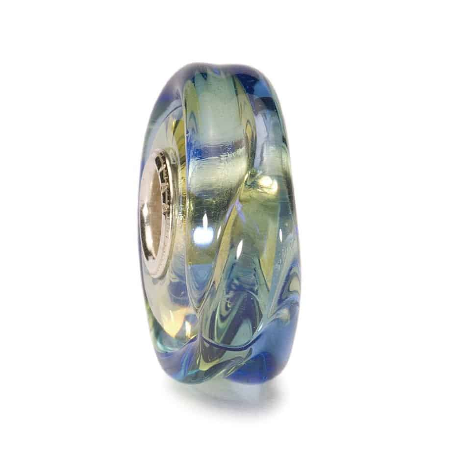 Trollbeads glass bead for modern charm bracelet with blue raised swirls of glass over a pale yellow background