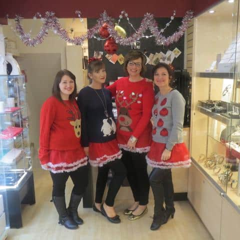 Four ladies on a shop floor with Christmas outfits on